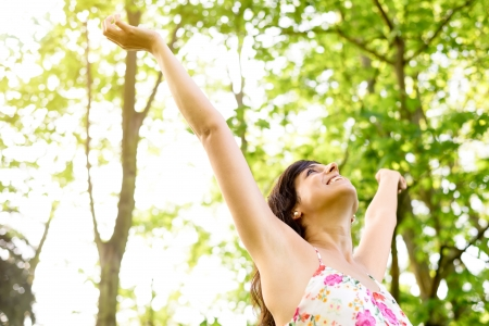 Photo pour Happy and carefree woman raising arms  to the sky on fresh bright spring greenery. Caucasian beautiful girl happiness and relaxation on nature. - image libre de droit