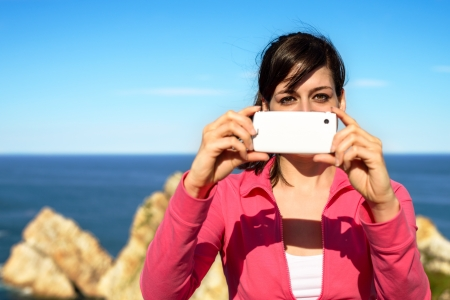 Photo pour Tourist woman taking photo with cellphone and having fun on summer travel. Brunette girl smiling and taking snapshot on coast landscape. - image libre de droit