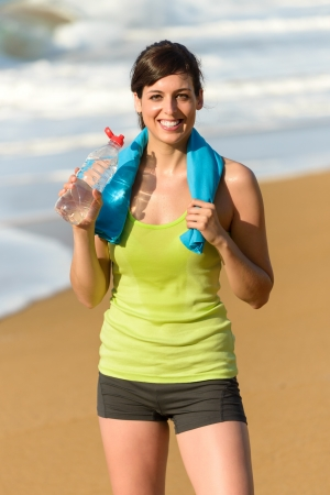 Photo pour Happy fitness beautiful woman drinking water and sweating after exercising on summer hot day in beach - image libre de droit