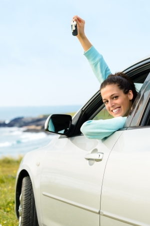 Woman driving car and holding keys on summer travel