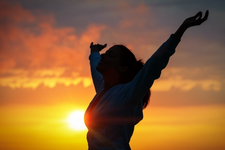 Free woman raising arms to golden sunset