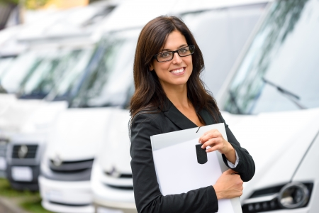 Successful sales business woman in van transport trade fair. Commercial exhibition and rental vehicle concept. Beautiful female seller or salesman holding car keys.