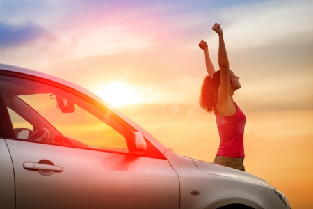 Foto de Female driver beside car raising arms and feeling the freedom of driving towards the sunset.  Woman and vehicle on beautiful sunshine background. - Imagen libre de derechos