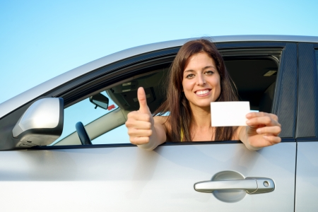 Female young car driver going thumbs up after passing the driving license test  Successful woman showing blank card and smiling in vehicle