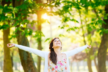 Blissful woman enjoying freedom and life in park on spring