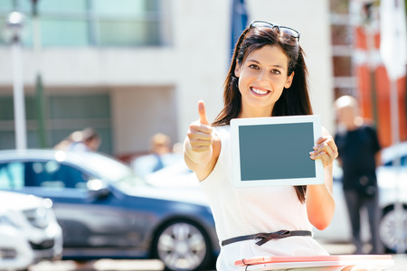 Female car sales consultant in business trade fair showing blank digital tablet screen and approving with thumbs up  Vehicle offer and information concept