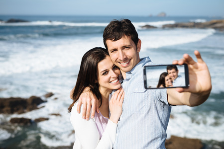 Young couple on honeymoon travel in Asturias coast, Spain, taking selfie portrait photo with smartphone camera の写真素材