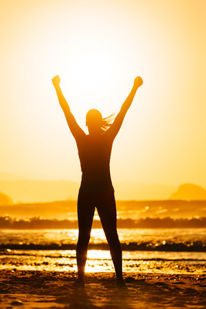 Fitness woman celebrating sport success on beautiful summer sunset or morning on the beach   Successful female runner silhouette raising arms to the sun