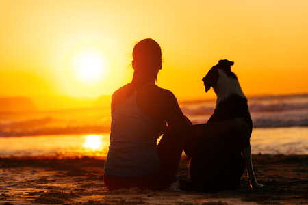 Relaxed woman and dog enjoying summer sunset or sunrise over the sea sitting on the sand at the beach