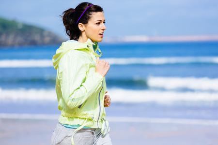 Fitness brunette woman running at Gijon beach, Asturias, Spain  Female runner training outdoor on spring sunny day