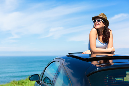 Foto de Relaxed happy woman on summer travel vacation to the coast  leaning out car sunroof with the sea on background  - Imagen libre de derechos