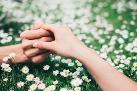 Young romantic  lovers holding hands gently on spring flowers field  Love and affection concept