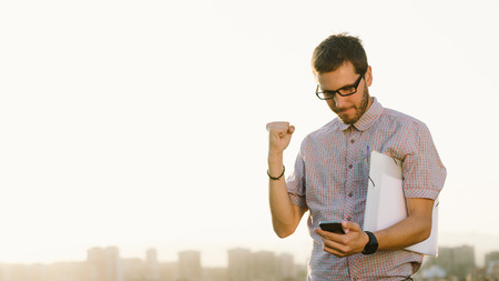 Photo for Successful professional casual man gesturing and checking cellphone messages towards city skyline. Entrepreneur enjoys success in job. - Royalty Free Image