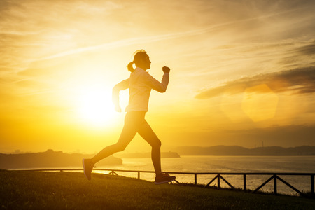 Photo pour Female athlete running outdoor towards the sea on beautiful golden sunset or sunrise. Asian female runner training on shining sun and lens flare background. - image libre de droit