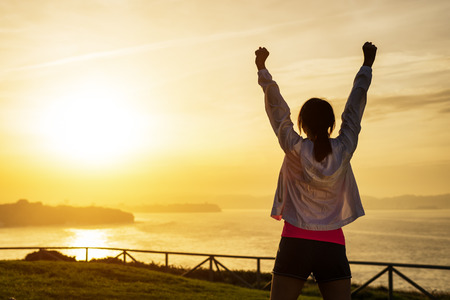 Photo pour Successful sporty woman raising arms towards golden beautiful sunset and sea. Female athlete celebrating sport success and goals. Healthy lifestyle and freedom concept. - image libre de droit