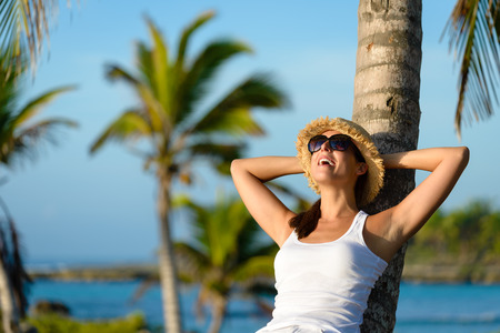 Woman on caribbean travel enjoying under tropical palm trees. Happy brunette enjoying vacation and tranquility.