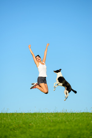 Joyful sporty woman and dog jumping and having fun after running and exercising outdoor together. Female athlete and her pet celebrating sport success and freedom.