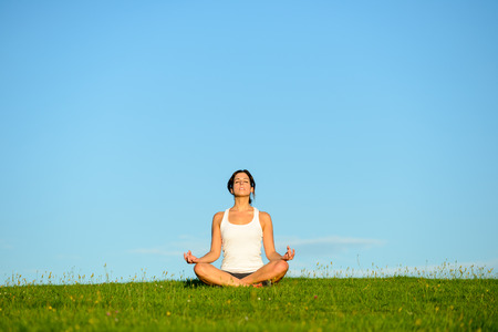 Young woman doing yoga relaxing and breathing exercise outdoor. Relax and tranquility at green grass field towards blue clear sky.
