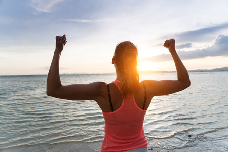 Sporty strong woman raising arms and enjoying freedom and success towards the sun and sea on sunset at the beach. Successful female athlete against the sun.の写真素材