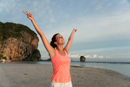 Motivated sporty woman celebrating workout success at the beach, Krabi, Thailand. Female athlete raising arms and enjoying freedom.