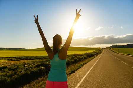 Photo pour Woman celebrating running and training success on countryside road during sunset or sunrise. Female runner raising arms towards the sun. - image libre de droit