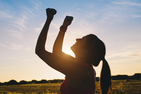 Photo pour Woman raising arms for celebrating fitness outdoor workout success. Motivation and healthy lifestyle goals concept. - image libre de droit