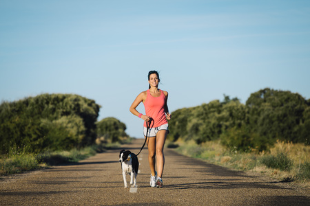 Sporty woman and dog running together on country road on summer sunset. Cheerful female athlete training and exercising outdoor with her pet.の写真素材