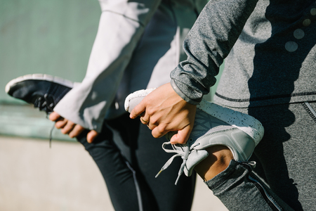 Photo pour Women stretching for warming up before running or working out. Fitness and healthy lifestyle concept. - image libre de droit