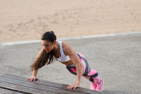 Photo for Strong fitness woman doing push ups for chest and arms strength workout. Female muscular motivated athlete training outside. - Royalty Free Image