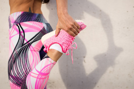 Foto de Urban fashion running running sportswear. Female athlete stretching legs after exercising. Healthy lifestyle and sport concept. - Imagen libre de derechos