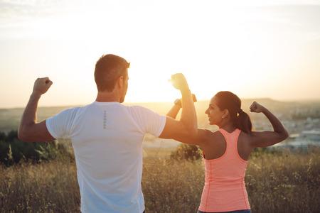Foto de Couple of athletes flexing biceps towards the sunset. Couple of athletes celebrating running outdoor workout success. - Imagen libre de derechos