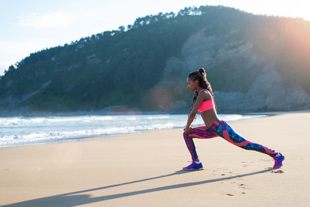 Foto de Fitness woman stretching legs or doing lunges at the beach. Black Female athlete doing relaxing exercise towards the sea. - Imagen libre de derechos