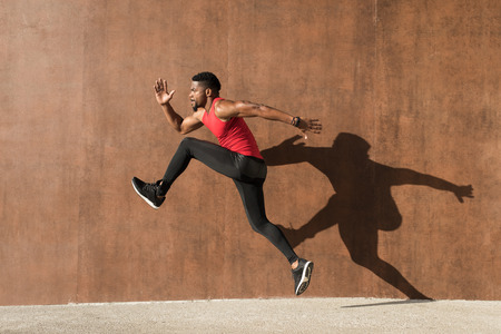 Photo for Young black man running and jumping casting shadow on a wall. - Royalty Free Image