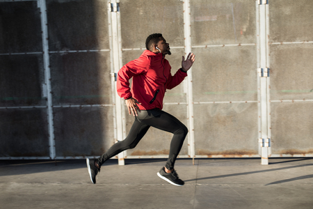 Photo pour Young black man running fast in the city. - image libre de droit
