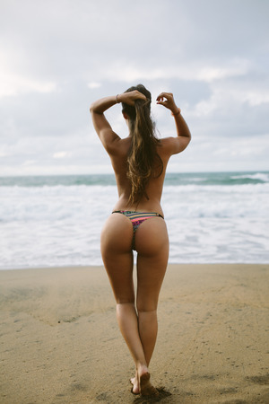 Foto de Back view of topless woman at beach towards the sea. Summer vacation relax and female freedom concept. - Imagen libre de derechos