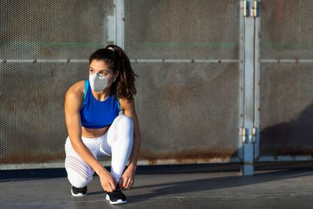 Photo for Young female athlete with face mask for protecting against Covid-19 getting ready for urban running and fitness workout. - Royalty Free Image
