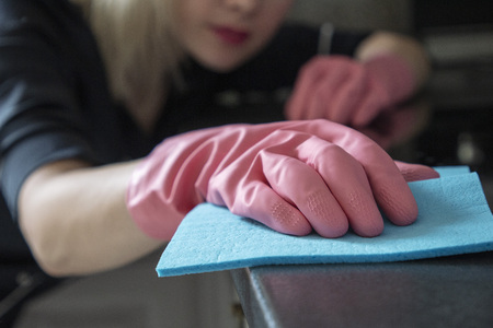 beautiful girl in rubber gloves does the cleaning in the apartment with a smile and good mood