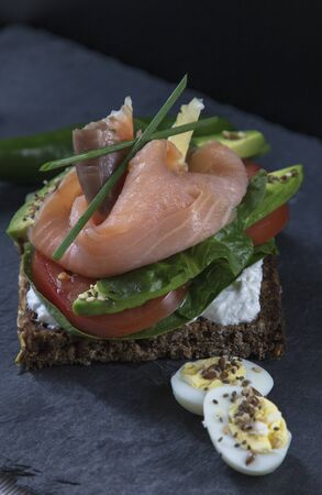 beautiful fresh sandwich with avocado and red fish, on brown bread, quail eggs, vegetarian sandwich