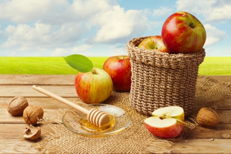 Apples with honey on wooden table over green meadow