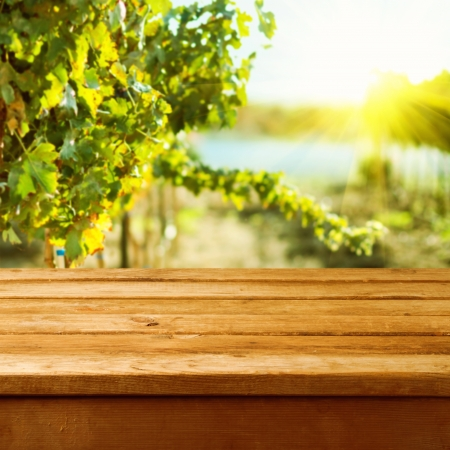 Empty wooden deck table over vineyard bokeh backgroundの写真素材