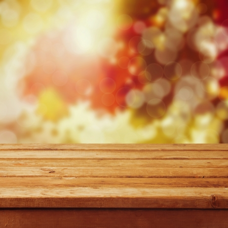 Empty wooden table over autumn leaves bokeh background. Ready for product montageの写真素材