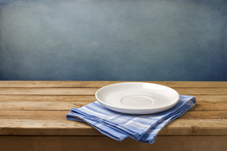 Empty plate on tablecloth on wooden table over grunge blue background