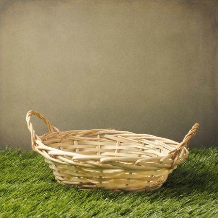 Empty basket on grass over grunge background