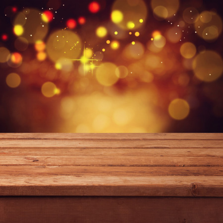 Christmas bokeh background with empty wooden tableの写真素材