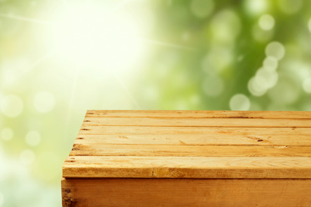Empty wooden table over garden bokeh background
