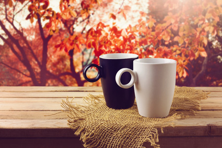 White and black cup with beverage on wooden table over beautiful nature background