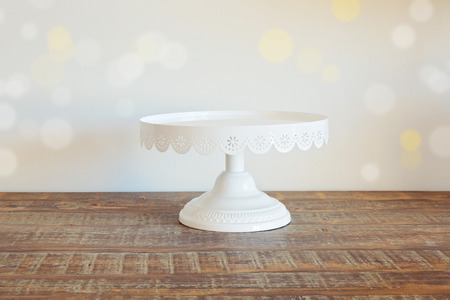 Cake plate on vintage wooden table over bokeh