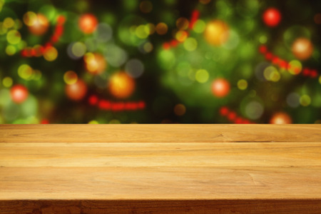 Empty wooden deck table over Christmas tree bokeh background