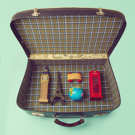 Summer vacation concept with suitcase and souvenirs from around the world