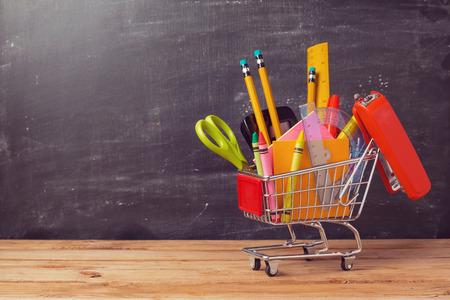Foto de Shopping cart with school supplies over chalkboard background. Back to school sale concept - Imagen libre de derechos
